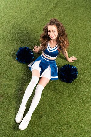 overhead view of smiling cheerleader girl in blue uniform sitting with pompoms on green field