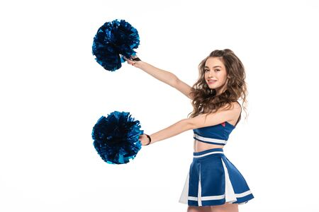 side view of happy cheerleader girl in blue uniform dancing with pompoms isolated on white