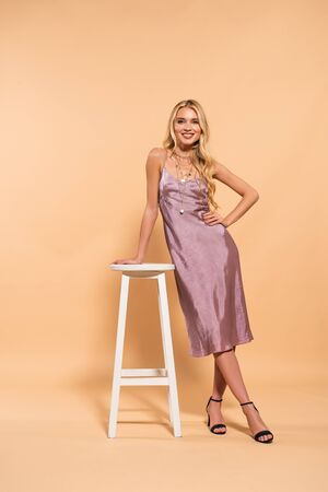 beautiful smiling blonde woman in violet satin dress posing near white high chair on beige background