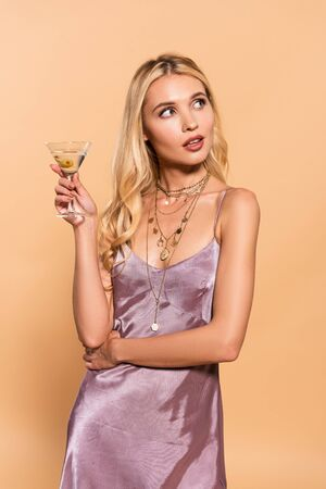 dreamy elegant blonde woman in violet satin dress and necklace holding cocktail isolated on beige