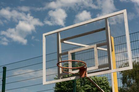 basketball hoop at basketball court under blue cloudy sky