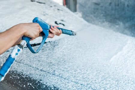 selective focus of car cleaner holding pressure washer with foam near car