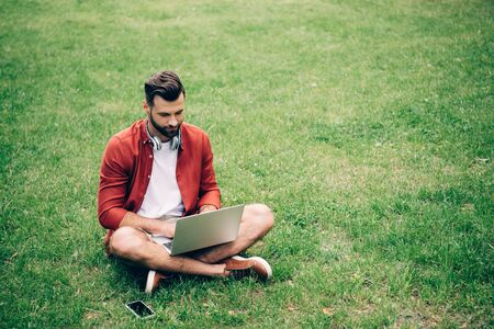 man sitting on grass in park near smartphone and using laptop