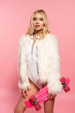sexy blonde girl in white bodysuit, faux fur coat with penny board on pink Фото со стока