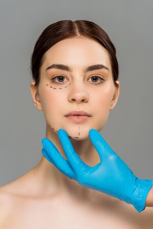 cropped view of plastic surgeon in latex glove touching face of attractive woman isolated on grey 스톡 콘텐츠