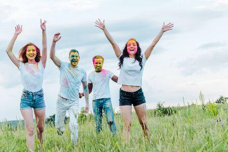 glückliche multikulturelle Freunde mit bunten Holi-Farben auf Gesichtern, die gestikulieren, während sie draußen stehen