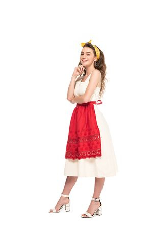 full length view of happy young housewife in dress and apron posing isolated on white