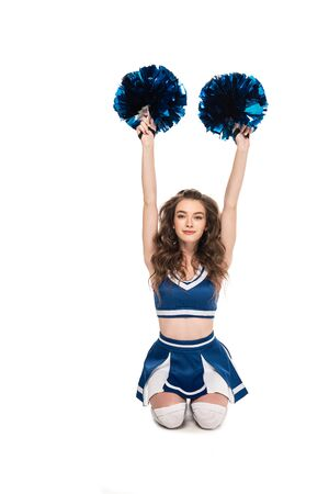 cheerleader girl in blue uniform sitting with pompoms and hands in air on floor isolated on white Banque d'images - 128288051