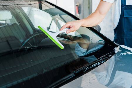 cropped view of car cleaner holding squeegee while washing car window Foto de archivo - 128288077
