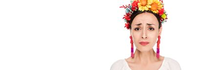 upset brunette young woman in national Ukrainian embroidered shirt and floral wreath isolated on white, panoramic shot