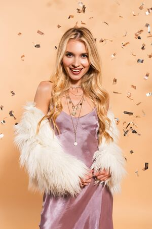 happy blonde woman in violet satin dress and faux fur coat standing under silver falling confetti on beige background Stock Photo