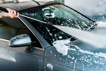 cropped view of car cleaner holding pressure washer with water near automobile
