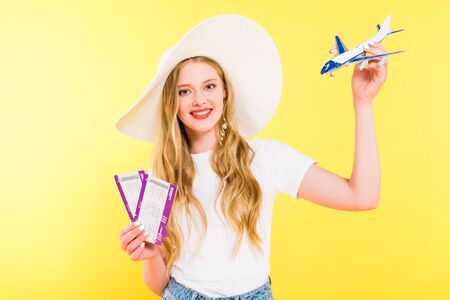 beautiful girl with plane model and air tickets On yellow Stock Photo