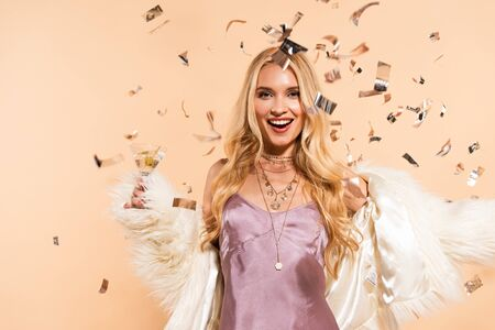 excited blonde woman in violet satin dress and faux fur coat standing under silver falling confetti on beige background Stock Photo