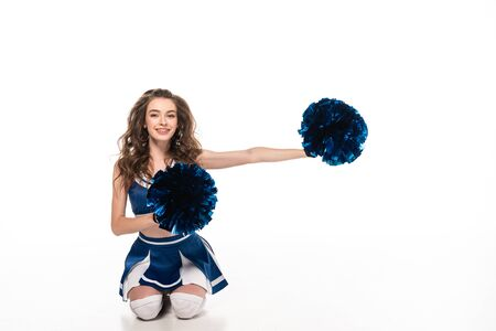 happy cheerleader girl in blue uniform sitting with pompoms on floor isolated on white Banque d'images - 128288446