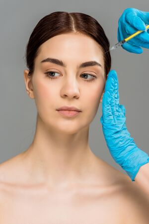 cropped view of plastic surgeon making beauty injection to attractive naked woman isolated on grey 写真素材 - 128288770