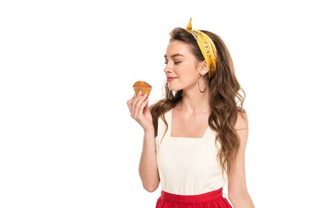 young pleased housewife in dress and apron looking at muffin isolated on white Standard-Bild