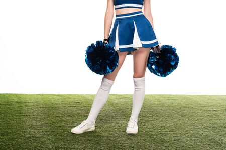 cropped view of sexy cheerleader girl in blue skirt and gaiters with pompoms on green field isolated on white Banque d'images - 128150331