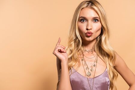 elegant blonde woman in violet satin dress and necklace with duck face isolated on beige