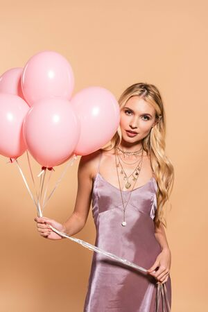 elegant blonde woman in violet satin dress and necklace holding pink balloons on beige