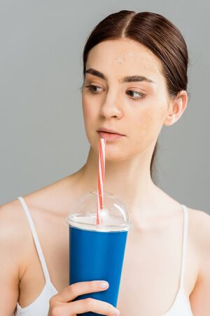 young woman with problem skin holding plastic cup isolated on grey