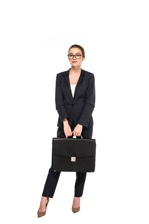 full length view of young businesswoman in black suit and glasses with briefcase isolated on white
