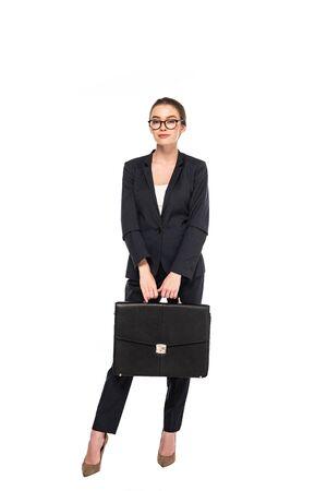 Vue sur toute la longueur d'une jeune femme d'affaires en costume noir et lunettes avec porte-documents isolé sur blanc