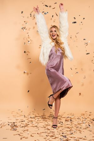 happy blonde woman in violet satin dress and faux fur coat dancing under silver falling confetti on beige background Stock Photo
