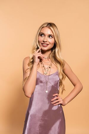 dreamy elegant blonde woman in violet satin dress and necklace posing on beige 版權商用圖片