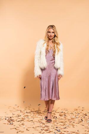 blonde woman in violet satin dress and faux fur coat standing under silver falling confetti on beige background Stock Photo