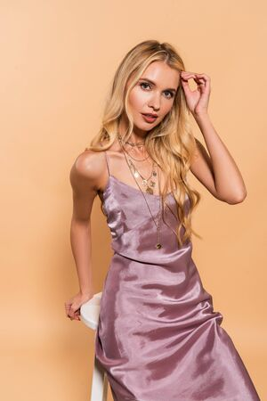 beautiful blonde woman in violet satin dress posing on white high chair on beige background 스톡 콘텐츠