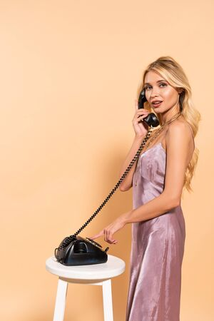 beautiful blonde woman in violet satin dress talking on black retro phone on beige background