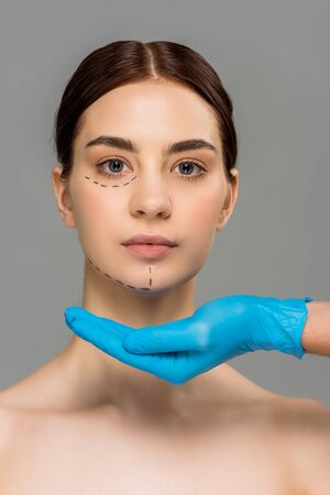 cropped view of plastic surgeon in latex glove with cupped hand near beautiful naked woman isolated on grey 스톡 콘텐츠