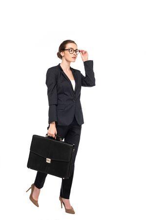 Ganzkörperansicht einer erfolgreichen Geschäftsfrau in schwarzem Anzug und Brille mit Aktentasche isoliert auf weiß
