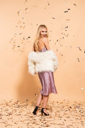 back view of happy blonde woman in violet satin dress and faux fur coat standing under silver falling confetti on beige background