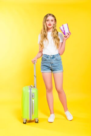beautiful girl with suitcase and air tickets On yellow Stock Photo