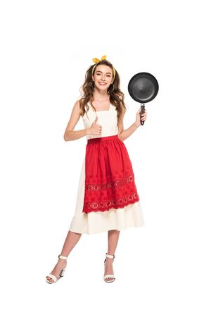 full length view of young housewife in dress and apron holding frying pan and showing thumb up isolated on white