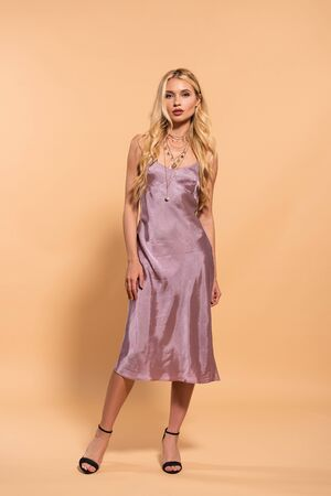 elegant blonde woman in violet satin dress and necklace posing on beige