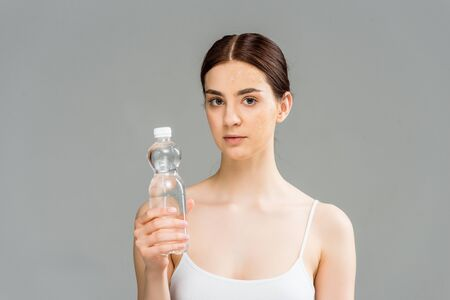 young woman with problem skin holding bottle with water isolated on grey Reklamní fotografie