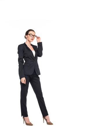full length view of young successful businesswoman in black suit and glasses isolated on white