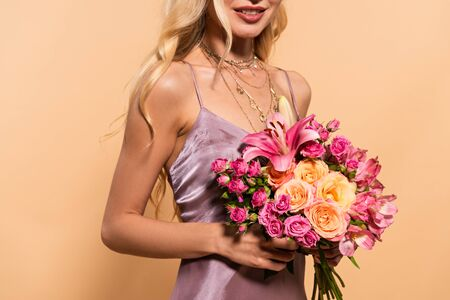 cropped view of elegant blonde woman in violet satin dress holding bouquet of flowers isolated on beige