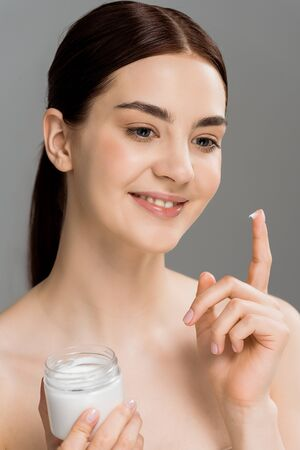 happy woman holding container with cosmetic cream isolated on grey
