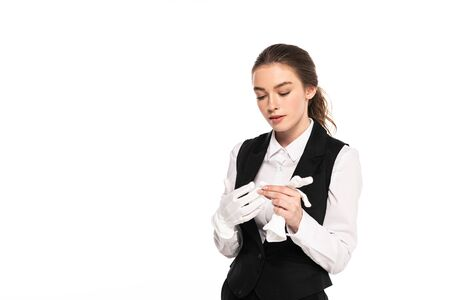 young waitress in formal wear looking at white gloves isolated on white
