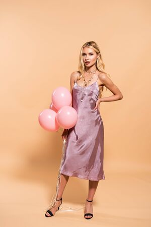 elegant blonde woman with hand on hip in violet satin dress and necklace holding pink balloons on beige