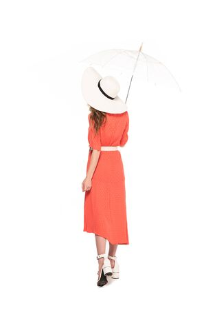 back view of elegant woman in hat and dress holding transparent umbrella isolated on white