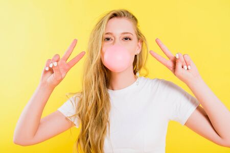 beautiful girl blowing bubble gum and doing peace signs Isolated On yellow