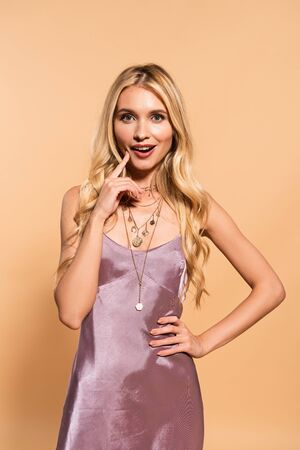 happy elegant blonde woman in violet satin dress and necklace posing with hand on hip on beige Banco de Imagens