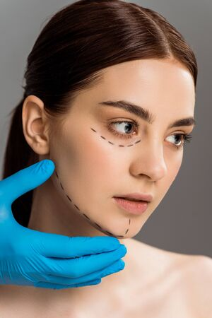cropped view of plastic surgeon in latex glove touching face of pretty naked woman isolated on grey