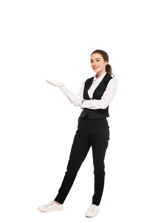 full length view of young waitress in formal wear and white gloves pointing with hand isolated on white Foto de archivo