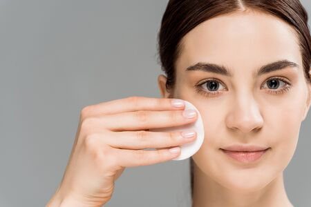 beautiful naked woman cleaning face with cotton pad isolated on grey